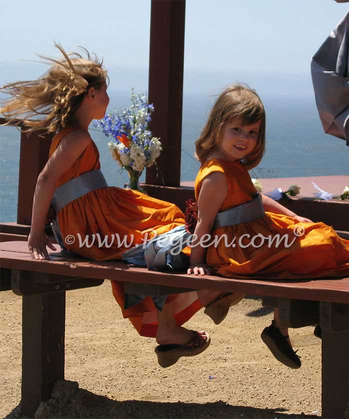 Powder blue and tangerine silk flower girl dresses at beach wedding